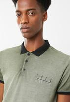 S.P.C.C. - Dirty dye pique golfer with binding - green & black