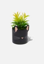 Typo - Shaped planter with plant - black