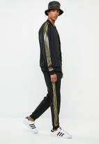 adidas Originals - SST50 track pants 24k - black & gold